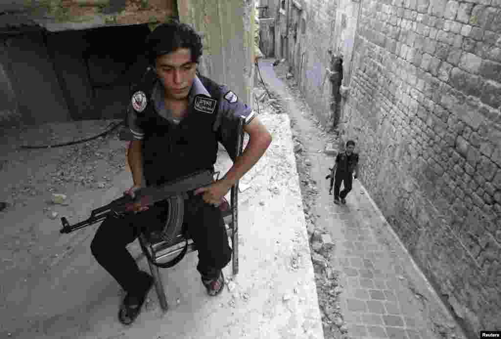 A Free Syrian Army fighter sits on a chair as a fellow fighter walks around Hanano Barracks in Aleppo, Sept. 10, 2013.