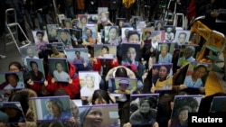 "FILE - Students hold portraits of deceased former South Korean ""comfort women"" during a rally in front of Japanese embassy in Seoul, South Korea, December 30, 2015."