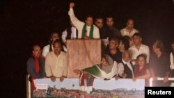 Pakistani opposition politician Imran Khan (C) waves while addressing supporters in Islamabad August 17, 2014.