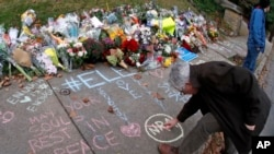 A man adds his comments to a spontaneous memorial of flowers and sidewalk writing that has appeared a block from the Tree of Life Synagogue on Monday, Oct. 29, 2018. (AP Photo/Gene J. Puskar)