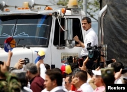 FILE - Venezuelan opposition leader Juan Guaido, whom many nations have recognized as the country's rightful interim ruler, stands on a truck carrying humanitarian aid for Venezuela, in Cucuta, Colombia, Feb. 23, 2019.