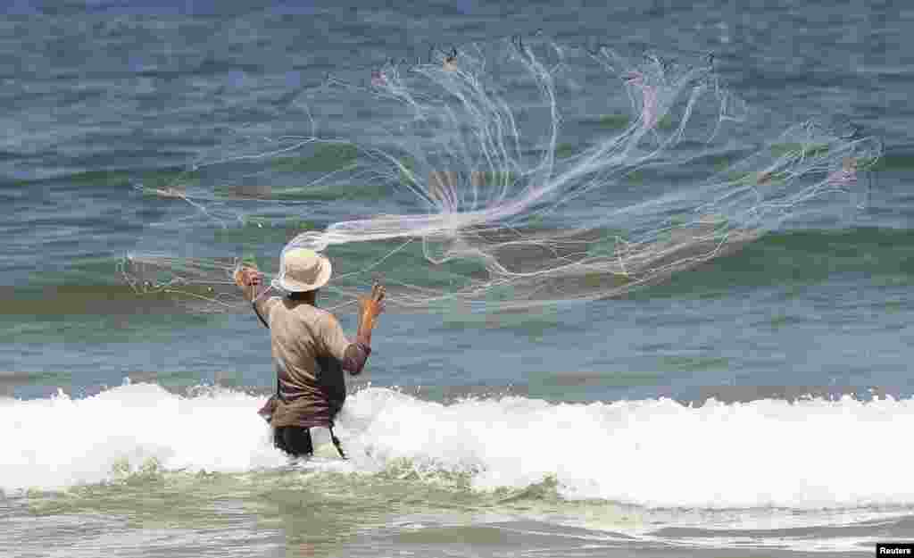 A Palestinian fisherman casts his net at a beach in Gaza City. Israel permits Gaza fishermen to head out to sea from 3 miles to 6 miles, restoring a limit it cut in half two months ago in response to rocket fire from the Palestinian enclave.