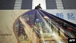 Công nhân treo một tấm quảng cáo khổng lồ trên tòa nhà chọc trời tại trung tâm thương mại ở Bắc Kinh
