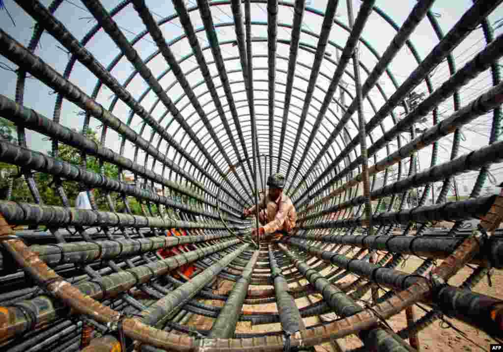 25/5: Một công nhân gắn các thanh sắt thành một cột tại một địa điểm xây dựng ở Lahore, Pakistan. (Reuters)