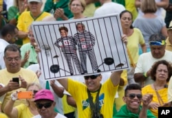 FILE - A demonstrator holds a poster with the photo of Brazilian president Dilma Rousseff and former President Luiz Inacio Lula da Silva in prison stripes during a protest on Copacabana beach in Rio de Janeiro, Brazil, March 13, 2016.