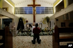 A person prays in Our Lady of Fatima Church in Poza Rica, Veracruz state, Mexico, Sept. 20, 2016. Two of the church's priests were found dead Monday, and were last seen Sunday. Their bullet-ridden bodies were found on a roadside.