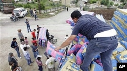 2011年5月,逃到黎巴嫩的敘利亞難民接受敘利亞社工(右)提供的床上用品(資料照)