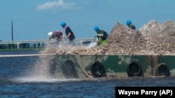 In this June 29, 2021 photo, workers on a large flat boat (called a barge) put 680 bushels of clam and oyster shells into the Mullica River in Port Republic, New Jersey. (AP Photo/Wayne Parry)