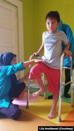 """Aksan Rana Bumi (8 tahun), penyintas kanker anak, sedang menjalani okupasi terapi dan fisioterapi di Klinik Tumbuh Kembang Anak """"Griya Fisio Bunda Novy"""" di Sleman, Yogyakarta. 28 November 2019 (Foto: Lila Imeldasari/Koleksi Pribadi)"""