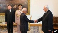 Foto de archivo en que el presidente interino Adly Mansour (derecha) saluda al primer ministro Hazem el-Beblawi, quien renunció.