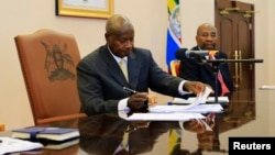 Uganda President Yoweri Museveni signs an anti-homosexual bill into law at the state house in Entebbe, 36 km south west of capital Kampala February 24, 2014.