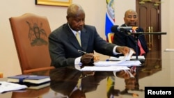 FILE - Uganda President Yoweri Museveni signs an anti-homosexual bill into law at the state house in Entebbe, 36 km (22 miles) south west of capital Kampala, Feb. 24, 2014.