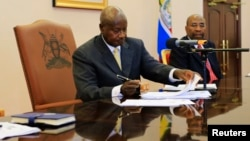 Uganda President Yoweri Museveni signs an anti-homosexual bill into law at the state house in Entebbe, 36 km (22 miles) south west of capital Kampala February 24, 2014. Museveni signed into law on Monday an anti-gay bill that toughens already strict legis