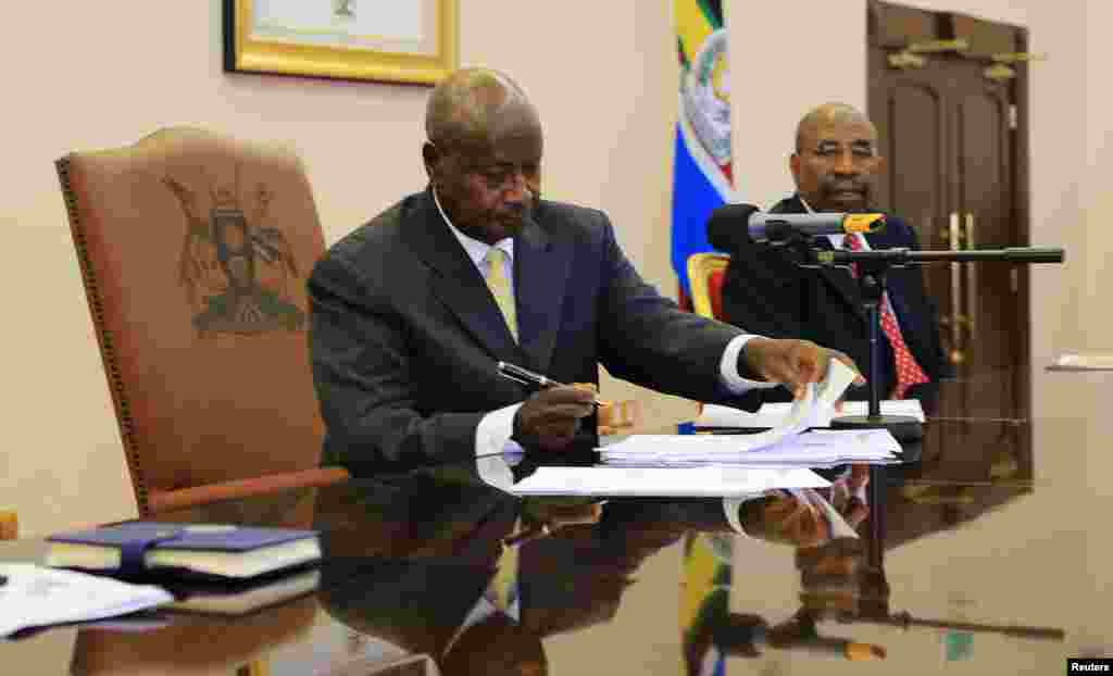Uganda President Yoweri Museveni signs an anti-homosexual bill into law at the state house in Entebbe, 36 km (22 miles) south west of capital Kampala.
