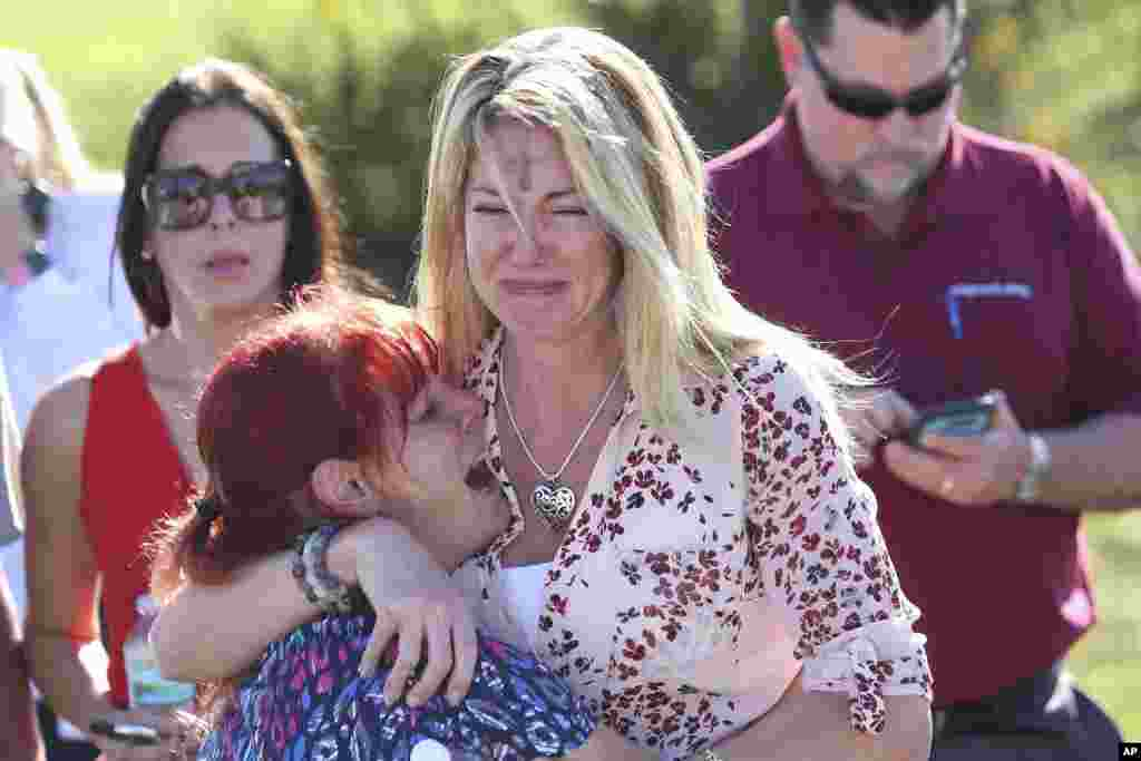 Parents wait for news after a report of a shooting at Marjory Stoneman Douglas High School in Parkland, Florida, Feb. 14, 2018.