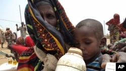 A mother quenches her child's thirst while waiting for food handouts at a health center in drought-stricken remote Somali region of Eastern Ethiopia, also known as the Ogaden, July 9, 2011.