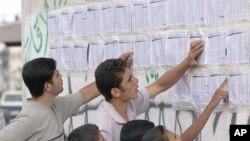 Des jeunes palestiniens consultant les listes de chômeurs devant recevoir des allocations de l'Autorité palestinienne