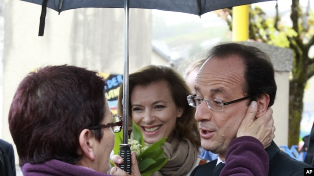 Socialist Party candidate for the presidential election Francois Hollande meets a resident with his companion Valerie Trierweiler, center, as he tours Tulle, after voting , May 6, 2012.