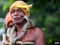 بھارتی علاقے جھاڑکھنڈ میں سانپوں کے میلے میں ایک سنپیرا اپنے سانپوں کے ساتھ، 2018