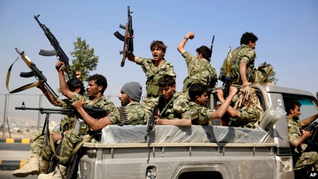 FILE - Shiite fighters, known as Houthis, ride on a patrol truck as they chant slogans during a tribal gathering showing support for the Houthi movement in Sanaa, Yemen.