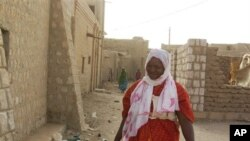 A young woman wears a headscarf in accordance with the directives of Islamist group Ansar Dine, which is seeking to impose Shariah law on Mali's Tuareg-occupied north, as she walks along an alley in Timbuktu, Mali.