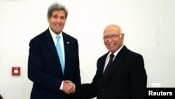 U.S. Secretary of State John Kerry shakes hands with Pakistan's National Security Advisor Sartaj Aziz (R) before a meeting in Islamabad, January 13, 2015.