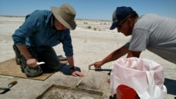 Archaeologist Daron Duke (L) and colleague Michael Shane work in this undated handout photo released on October 11, 2021 at an ancient hearth dating to 12,300 years ago at the Wishbone site in Great Salt Lake Desert in northern Utah. (Sarah K. Rice/Handout via REUTERS)