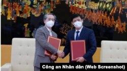 Bộ trưởng Bộ Y tế Nguyễn Thanh Long và Đại sứ Trung Quốc tại Hà Nội Hùng Ba trao biên bản bàn giao lô hàng 500.000 liều vaccine và hơn 500.000 bơm kim tiêm do Bắc Kinh tặng. (Ảnh Trần Minh - chụp từ màn hình Công an Nhân dân)