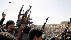 3일(현지시각) 리비아 동부 도시 아즈다비야에서 카다피軍에 대항하는 반군들이 정부군과 교전 중 숨진 이들을 위한 장례식 중 공중에 총을 발사하고 있다.