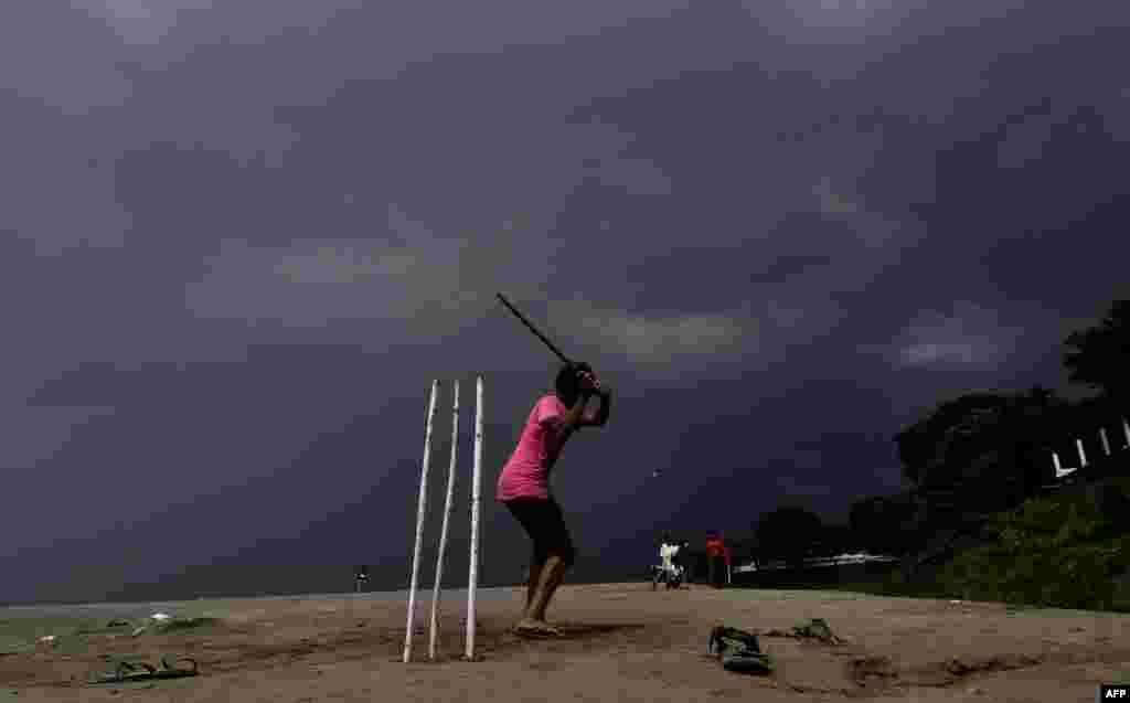 Children play cricket as rain clouds loom over the Brahmaputra River in Guwahati, capital of northeastern Assam state, India.