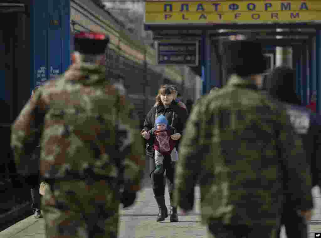 زنی با کودکش در حال عبور از صف نیروهای روسگرا در سکوی ایستگاه قطار سیمفروپل - ۱۴ مارس ۲۰۱۴