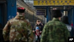 A woman walks with a baby as members of the Crimean self defense forces stand on the platform at the main railway station in Simferopol, Ukraine, March 14, 2014.