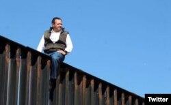 Braulio Guerra, legislador mexicano encima de una valla que divide la frontera entre EE.UU. y México.