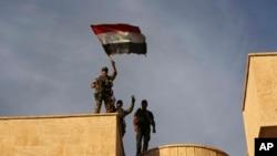 Iraq's elite counterterrorism force soldiers raise an Iraqi flag over the main church in Bartella, Iraq, Oct. 21, 2016.