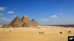 Les touristes sur des chameaux sur le site historique de la Pyramides de Gizeh à Gizeh, près du Caire, en Egypte, le jeudi 9 Avril 2015.