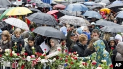 People place flowers near the entrance of a courthouse where the trial of Anders Behring Breivik is conducted, as thousands turn up in poor weather to sing a popular children's song in Oslo April 26, 2012.