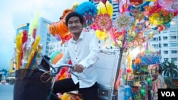 Pham Minh Dap, 24, sells balloons and children's toys outside a park in Hanoi, Aug. 7, 2014. (Marianne Brown/VOA)