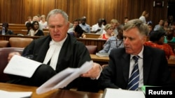 Oscar Pistorius's lawyers Barry Roux (L) and Brian Webber prepare documents before the start of the application to appeal some of his bail conditions at a Pretoria court in Pretoria, March 28, 2013.