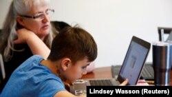 Seorang Ibu mendampingi putranya saat pembelajaran online dari rumah yang diberlakukan selama pandemi Covid-19 di kota Woodinville, Washington, AS (foto: ilustrasi).