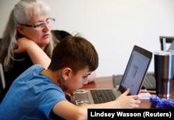 Siswa kelas 4 di Cottage Lake Elementary mencoba mencari tahu instruksi penugasan di laptop-nya saat pembelajaran online yang diterapkan di Distrik Northshore School selama dua minggu akibat corona, di Woodinville, Washington, AS, 11 Maret. 2020.