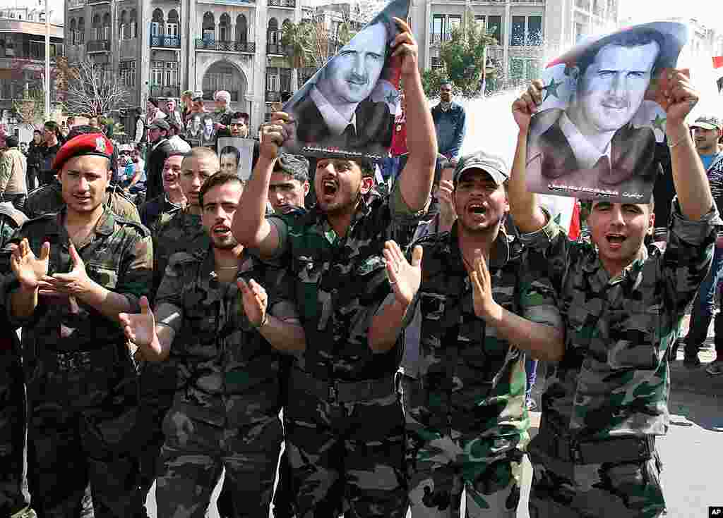 Syrian Army soldiers shout slogans and hold up portraits of Syrian President Bashar al- Assad during a pro-regime rally in Damascus, Syria, March 23, 2012. (AP)
