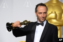 "FILE - Emmanuel Lubezki poses with the award for best cinematographer of the year for ""Gravity"" during the Oscars, March 2, 2014."