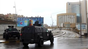 Libyan security forces and emergency services surround Tripoli's central Corinthia Hotel (R) in the Libyan capital,  Jan. 27, 2015.
