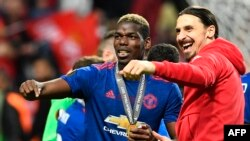 Le milieu de terrain français de Manchester United, Paul Pogba, célèbre sa médaille avec l'attaquant suédois de Manchester United Zlatan Ibrahimovic, à droite, après le dernier match de football de l'UEFA Europa League Ajax Amsterdam contre Manchester Uni