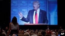 도널드 트럼프 공화당 대통령 후보가 8일 디트로이트 이코노믹 클럽에서 경제정책 구상을 밝히는 동안 한 청중이 자리에서 일어나 소리치고 있다.