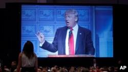 Một người biểu tình đứng trên ghế la hét trong lúc ông Trump đọc một bài diễn văn về chính sách kinh tế ở Detroit, 8/8/2016.
