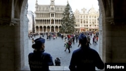 Belgian police officers stand guard on Brussels' Grand Place, December 29, 2015, after two people were arrested in Belgium on Sunday and Monday, both suspected of plotting an attack in Brussels on New Year's Eve, federal prosecutors said.