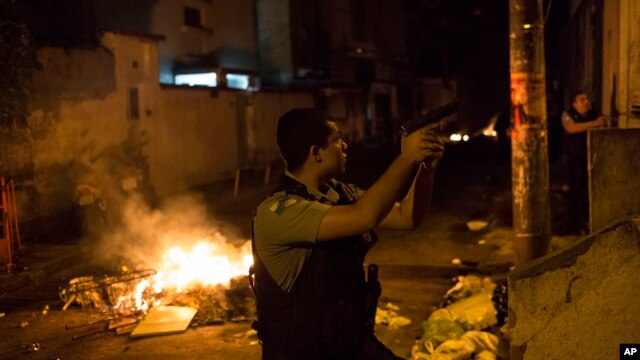 Officers of the Police Pacification Unit patrol next to a burning barricade during clashes at the Pavao Pavaozinho slum in Rio de Janeiro, Brazil, Tuesday, April 22, 2014.