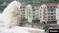 A wave, under the influence of Typhoon Chan-hom, hits the shore next to residential buildings in Wenling, Zhejiang province, China, July 10, 2015.