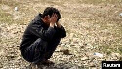 """一名伊拉克人蹲在地上掩面痛哭。在伊拉克军队与""""伊斯兰国""""激进分子在摩苏尔交战期间,他的儿子被空袭炸死。(2017年3月17日)"""